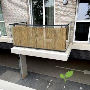 Glazen balkon met rietmat